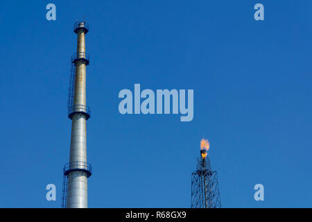 Gas flares in petroleum refinery  with blue sky background - Stock Photo