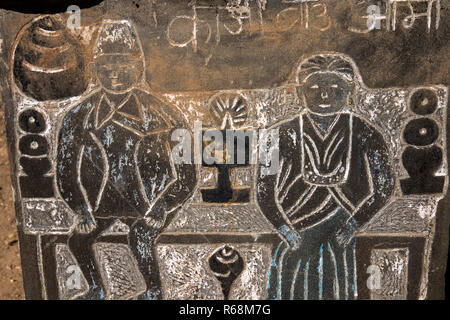 Nepal, Lukla, Lomdza, Buddhist folk art, figures of Nepali man and woman at temple altar carved in slate on Mani Wall - Stock Photo