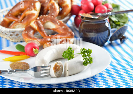Typical Bavarian white sausages with pretzels and sweet mustard - Stock Photo