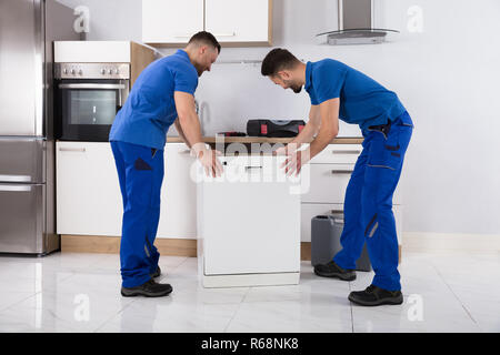 Two Movers Placing Dishwasher In Kitchen - Stock Photo