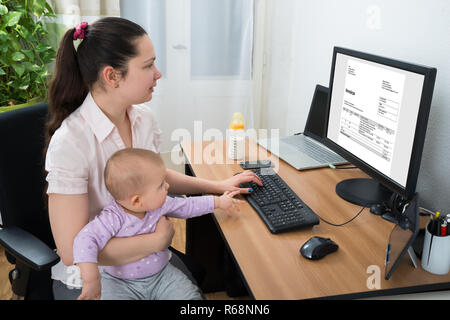 Woman Checking Bill On Computer - Stock Photo