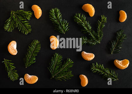 Flat lay pattern of orange mandarin slices and small fir branches on dark textured background. - Stock Photo