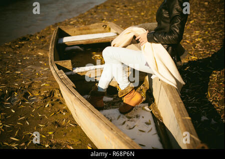 slim girl's legs in blue jeans and brown boots. girl sat on the upturned boat, on the shore, yellow autumn leaves - Stock Photo