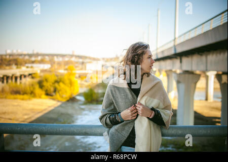 portrait of a beautiful young woman with long thin hair, a leather jacket, blue jeans. warm autumn sunny day on the stairs of the bridge. - Stock Photo