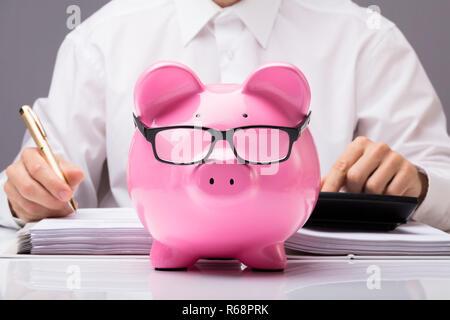 Businessman Calculating Tax With Piggybank - Stock Photo