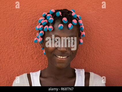Portrait of a Angolan girl with the typical hairstyle made of braids with colorful scrunchies, Benguela Province, Catumbela, Angola - Stock Photo
