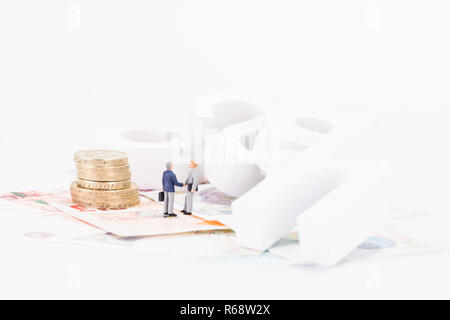 Miniature businessman shaking hands with cash wooden letters background - Stock Photo