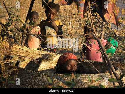 Woman making a big basket to store the corn, in a mwila tribe village, Huila Province, Chibia, Angola - Stock Photo