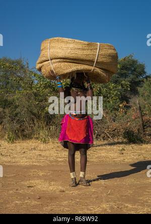 Muhakaona tribe woman carrying a basket on her head, Cunene Province, Oncocua, Angola - Stock Photo