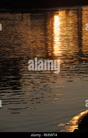 Sunrise reflects in the river Rhine. - Stock Photo