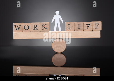 Human Figure Balancing Between Work And Life On Seesaw - Stock Photo