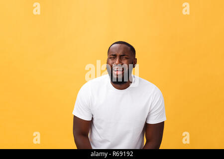 Young Stressed man with face showing sadness and despair. Isolated over yellow background. - Stock Photo