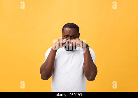 Young Stressed man with hand on his face showing sadness and despair. Isolated over yellow background. - Stock Photo