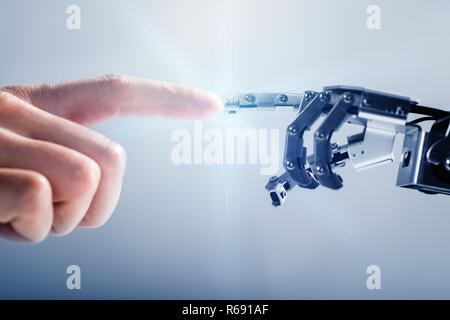 Businessperson's Finger Touching Robotic Finger - Stock Photo
