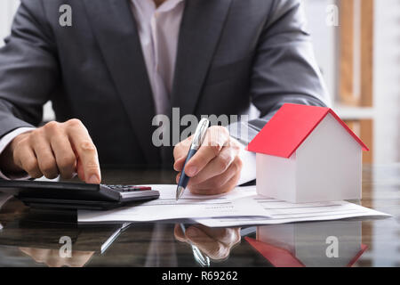 Businessperson Calculating Invoice With Calculator - Stock Photo