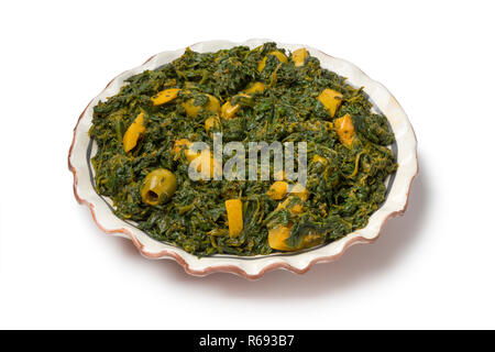 Dish with Moroccan style spinach salad with green olives and preserved lemon isolated on white background - Stock Photo