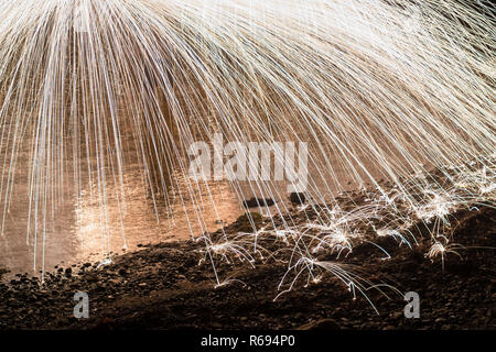 steel wool spinning over water and beach - Stock Photo