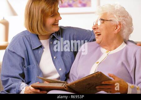 Portrait, alte Dame schaut mit ihrer Tochter ein Fotoalbum an - Stock Photo