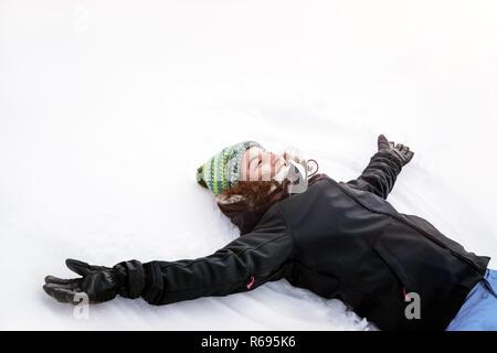 Happy girl making snow angel - Stock Photo