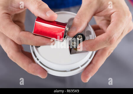 Person's Hand Inserting Battery In Smoke Detector - Stock Photo