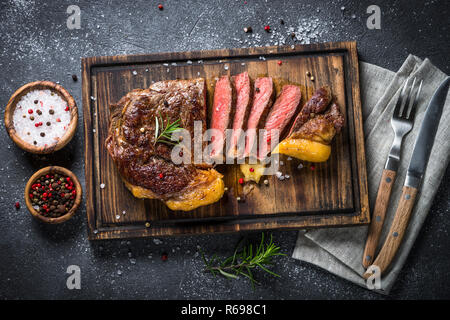 Grilled beef steak ribeye on wooden cutting board.  - Stock Photo