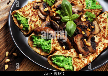 Savory Homemade Mushroom and Spinach Crepes with Cheese and avocado - Stock Photo
