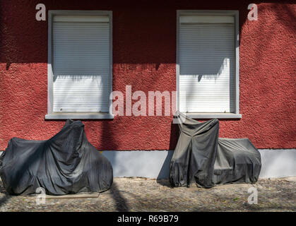 Covered Motorcycles Are Standing In Front Of A House Wall - Stock Photo