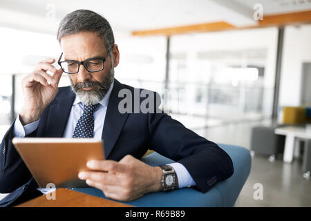 Shot of thinking financial advisor businessman working in office. - Stock Photo