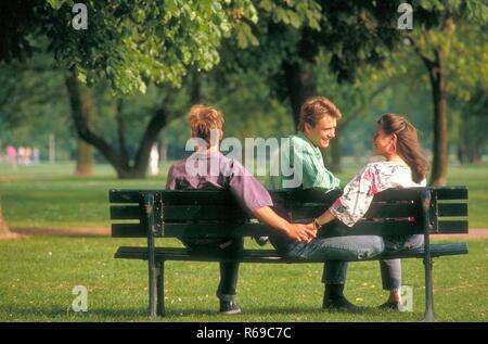 Portrait, Parkszene, junge Frau mit langen braunen Haaren flirtet mit 2 jungen Maennern auf einer Parkbank - Stock Photo
