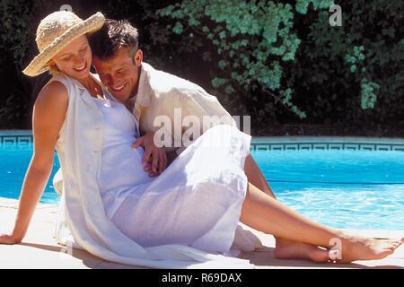Outdoor,Ganzfigur, blonder Mann und seine schwangere weiss gekleidete Frau mit Strohhut am Rand eines Schwimmbeckens - Stock Photo
