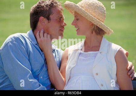 Outdoor, Parkszene, Profil, Mann im Jeanshemd und seine schwangere weiss gekleidete Frau mit Strohhut - Stock Photo