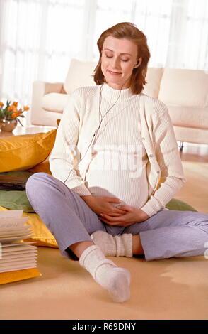 Portrait, schwangere Frau sitzt  auf dem Fussboden und hoert entspannt Musik - Stock Photo