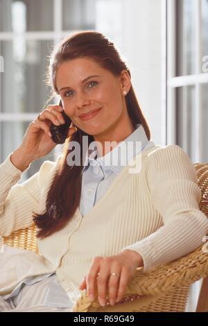Portrait, Innenraum, ca. 30 Jahre alte Frau mit langen braunen Haaren bekleidet mit hellem Hemd und Strickjacke  sitzt laechelnd auf einem Korbsessel vor einer Glastuer und telefoniert mit einem Handy - Stock Photo