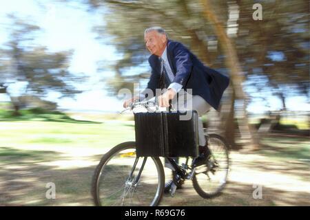 Outdoor, Ganzfigur, ca. 60 Jahre alter Mann, bekleidet mit blauer Anzugsjacke und hellgrauer Hose mit Aktentasche unterwegs auf dem Fahrrad - Stock Photo