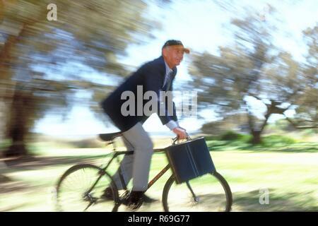 Outdoor, Ganzfigur, ca. 60 Jahre alter Mann, bekleidet mit blauer Anzugsjacke, heller Hose und Baseballkappe mit Aktentasche unterwegs mit dem Fahrrad - Stock Photo