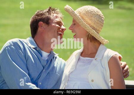 Outdoor, Parkszene, Profil, Mann im Jeanshemd und seine schwangere weiss gekleidete Frau mit Strohhut schauen sich lachend an - Stock Photo
