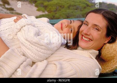 Portrait, Outdoor, bruenette Mutter und Tochter, 8 Jahre alt, beide bekleidet mit weissen Pullovern, liegen lachend zusammen auf einer Parkbank - Stock Photo
