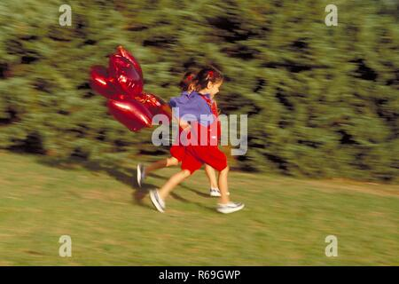 Parkszene, Ganzfigur, 2 bruenette Zwillings-Maedchen, 6 Jahre alt, bekleidet mit roter Latzhose, blauer Bluse und Turnschuhen laufen mit roten herzfoermigen Luftballons in der Hand an Bueschen vorbei ueber eine Wiese - Stock Photo