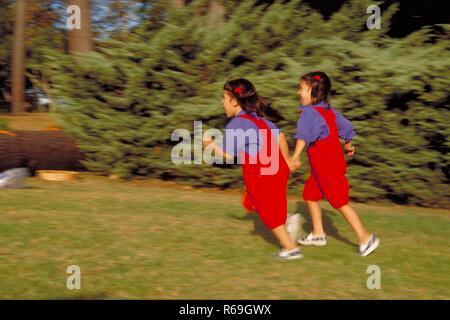 Parkszene, Ganzfigur, 2 bruenette Zwillings-Maedchen, 6 Jahre alt, bekleidet mit roter Latzhose, blauer Bluse und Turnschuhen rennen an Bueschen vorbei ueber eine Wiese - Stock Photo