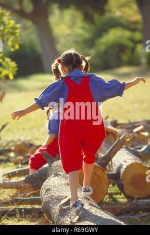 Parkszene, Ganzfigur, 2 bruenette Zwillings-Maedchen, 6 Jahre alt, bekleidet mit roter Latzhose, blauer Bluse und Turnschuhen balancieren ueber dicke Baumstaemme - Stock Photo