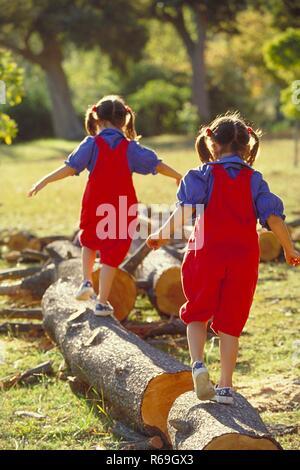 Parkszene, Ganzfigur von hinten, 2 bruenette Zwillings-Maedchen, 6 Jahre alt, bekleidet mit roter Latzhose, blauer Bluse und Turnschuhen balancieren ueber dicke Baumstaemme - Stock Photo
