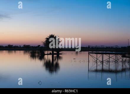 Palm Tree And Footbridge At A Lake At Dusk Hardap Namibia - Stock Photo