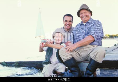 Portrait, Strandszene, 3 Generationen, Grossvater, Vater und Soh, 7 Jahre, sitzen mit Gummistiefeln und Hueten am Wasser, der Junge zeigt stolz sein Segelboot - Stock Photo