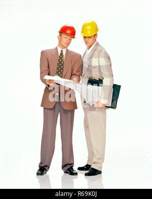 Portrait, Ganzfigur, 2 junge Maenner mit kurzen Haaren bekleidet mit Anzug, weissem Hemd, Krawatte und Schutzhelm, diskutieren Konstruktionsplan - Stock Photo