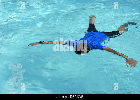 floating body of a drowned male children in swimming pool. concept of safety - Stock Photo