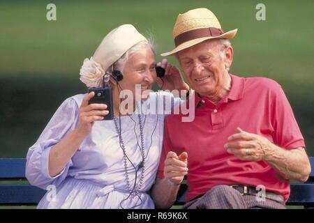 Portrait, Parkszene, Seniorenpaar, beide mit Hut, sitzen auf einer Bank und hoeren amuesiert Musik von einem Walkman gemeinsam ueber einen Kopfhoerer - Stock Photo