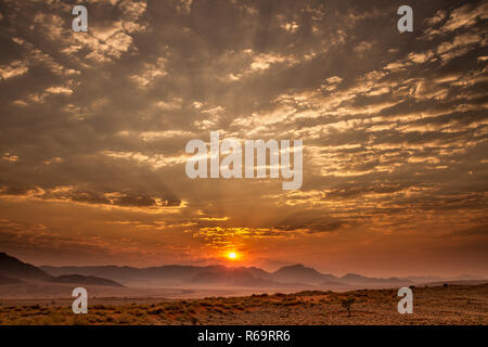 Sunrise with cloudy sky over the mountains, Namib dessert, Namibia - Stock Photo