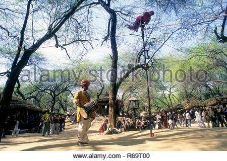 street performer balancing act on bamboo in surajkund Fair, faridabad, haryana, india - Stock Photo