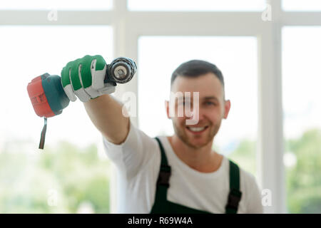 Cordless screwdriver in male hands - Stock Photo