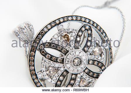 White gold pendant with diamonds on soft white background - Stock Photo